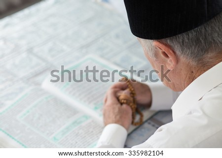 An old man reading the Koran. Selective focus