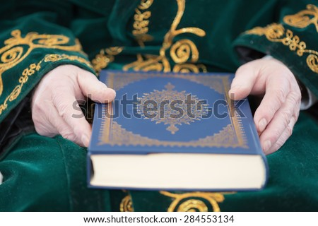 An old man's hands holding the quran book - stock photo