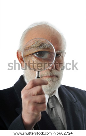 an old man sees through a magnifying lens - stock photo
