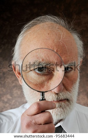 an old man sees through in magnifying lens in studio - stock photo