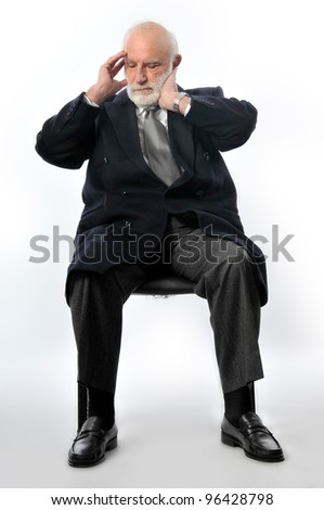 an old man sits in black chair and he holds his head - stock photo