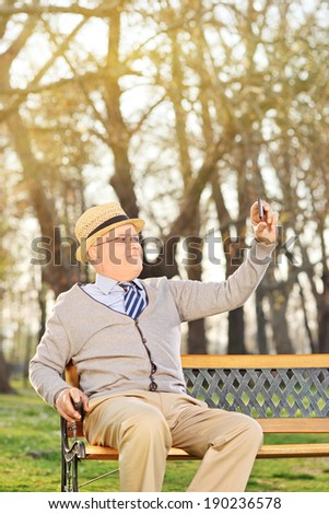 An old man taking a selfie with cell phone seated on bench outdoors - stock photo