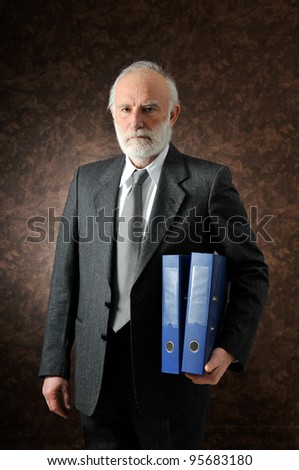 an old man who keeps two folder in studio - stock photo