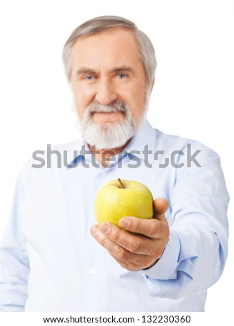 An old man with a beard holds out a yellow-green apple. Isolated on white background. - stock photo