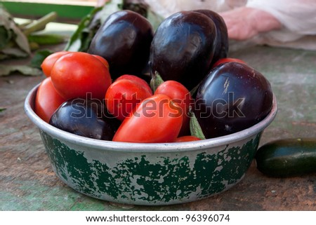 An old metal bowl sits on a rustic wooden table, filled with fresh, ripe eggplants and tomatoes. - stock photo
