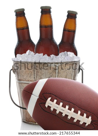 An old metal bucket with three brown beer bottles covered in condensation on a white background. An American football at an angle sits in front of the pail. - stock photo
