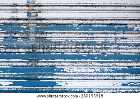 An old metal roll up door with weathered, cracked paint and rusting.  - stock photo