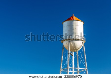 An old multi-column elevated water tower and water tank stands against a solid blue sky in a small town. - stock photo