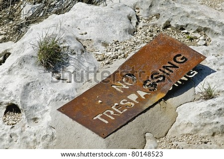 "An old ""No Trespassing"" sign laying on the ground in the Texas Hill Country"