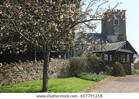 An old Norman church at Gittisham in the County of Devon early in Springtime, seen through the cherry blossoms