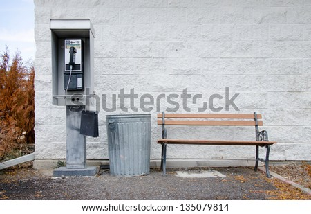 An old pay phone next to a metal trashcan and a wooden bench in front of a white painted cinderblock wall. - stock photo