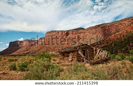 An old pioneer cabin sits in a red rock valley of Colorado. - stock photo