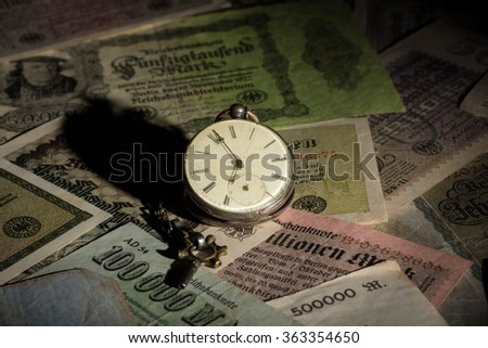 An old pocket watch on inflation money - stock photo
