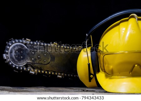 An old power saw for cutting wood. Chainsaw and protective clothing on a wooden workshop table. Black background.