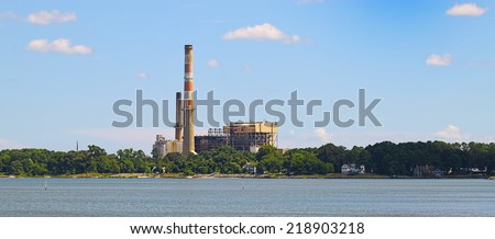 An old powerplant/oil refinary along the shoreline of the York river in Yorktown Virginia as seen from the USCG training center pier on a summer day