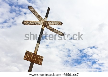 An old railway sign with a cloudy blue sky in the background. - stock photo