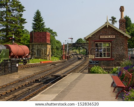 An old railway station with signal box, water tank and goods wagon - stock photo