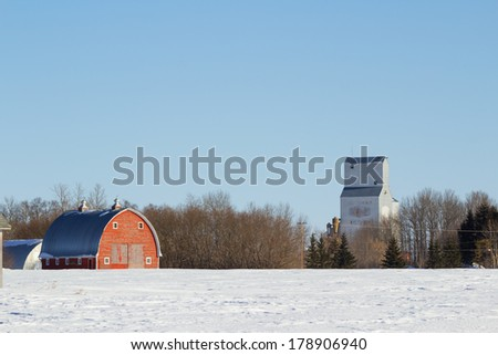An old red barn and an elevator - stock photo