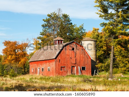 An old red barn with silo is surrounded by trees with colorful fall foliage. Shot in rural Wisconsin. - stock photo