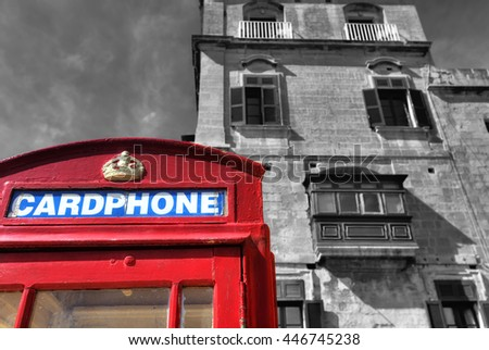 An old red cardphone booth in the historic city Valletta with an old appartment building in the background, with black and white background for a higher booth contrast