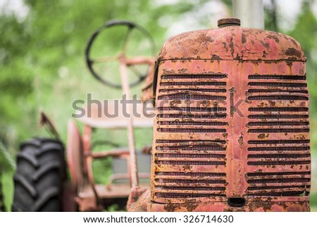 An old red farm tractor rusty and weathered from use. Shallow depth of field.