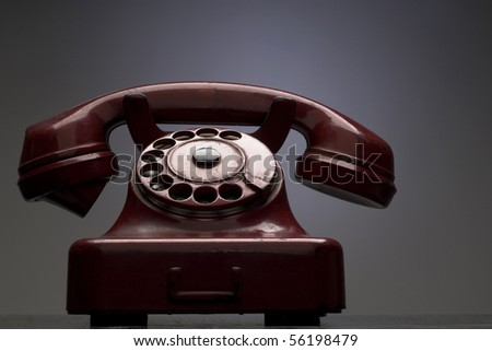 an old red telephone against gray background - stock photo