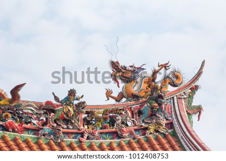 An old roof of Chinese temple with Dragon statue background of cloud and sky