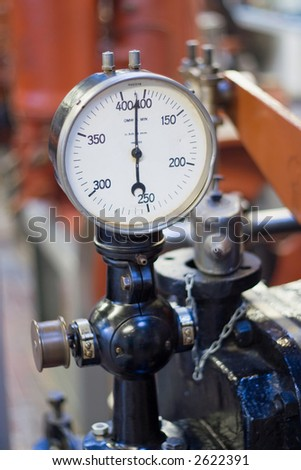 An old rotation gauge on an old ship motor. - stock photo