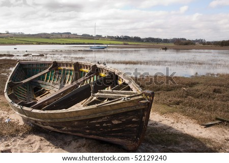 An old rowing boat in need of repair on the beach by the estuary