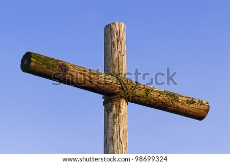 An old, rugged, wooden cross stands against a pure deep blue sky. - stock photo