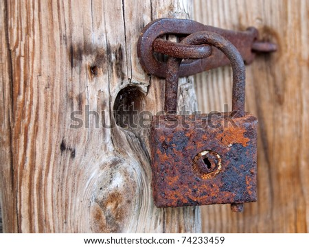 An old rusty lock on the door of an abandoned barn - stock photo