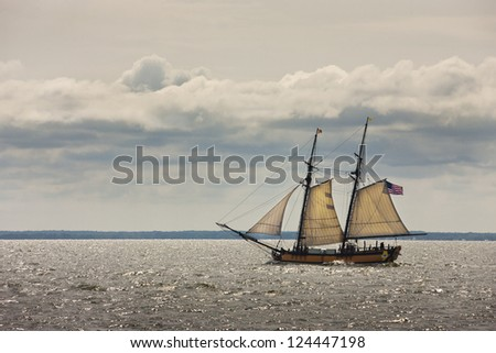 An old sailboat with an American flag passes by the camera.