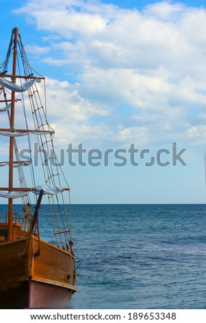 An old sailing ship at the pier on the background of sea and sky, with space for your writing - stock photo