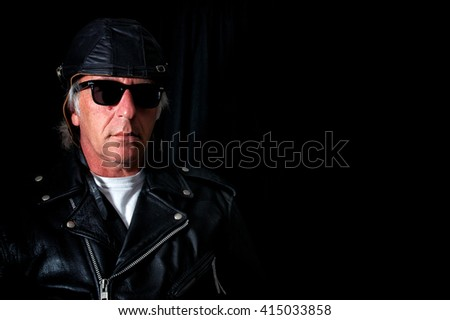 An old school biker wearing vintage leather jacket, retro sunglasses and leather aviator helmet looking serious against black backdrop. - stock photo