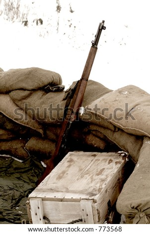 An old, sepia, and grainy WWII photo of a rifle, ammunition box and sandbags