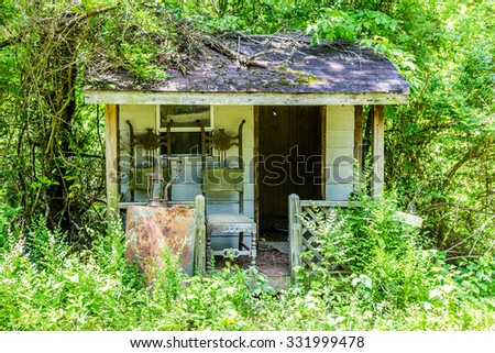 An Old Shack Overgrown in Woods with two chairs