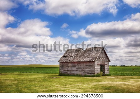 An old shed or similar kind of outbuilding on a farm in central Iowa stands before a field of early corn. - stock photo
