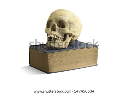 An old skull on top of an old book - stock photo