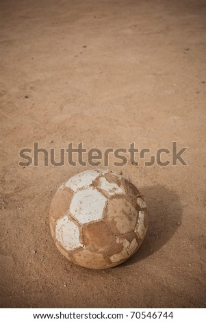 An old soccer ball on ground with copyspace - stock photo