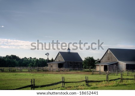 An old Stable and fences on a sunny day in Canada - stock photo