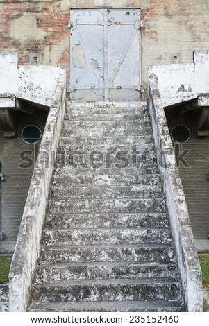 An Old Stair of Concrete Leading Up to A Steel Blast Door, in An Old Japanese Military Facility, Built in 1917,  Located in Kaohsiung, Taiwan. - stock photo