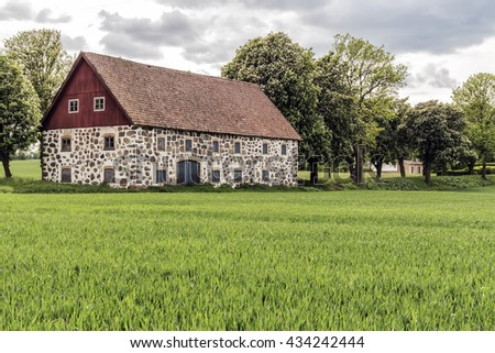 An old stone barn with wooden roof set in the rural countryside of Swedens Skane region. - stock photo