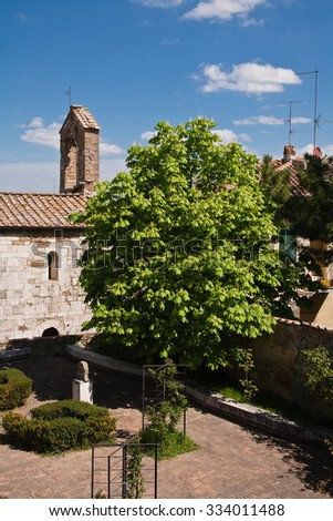An old stone roman church and a garden in San Quirico d'Orcia in Italy