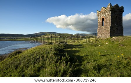 An old stone Watch tower over looking Dingle Bay Co. Kerry Ireland as a fishing boat heads out to sea - stock photo