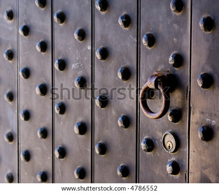 An old studded door opens by pulling a rusty ring.