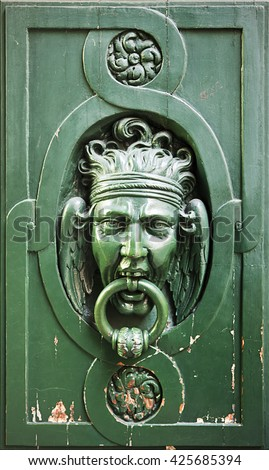An old-style knocker in Paris on a door with weathered paint peeling. The fantastical image of the man holding the wrought iron ring in his mouth evinces the pain in the image. - stock photo