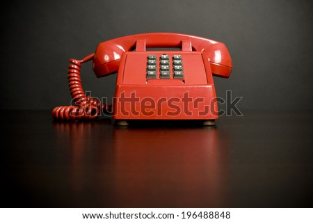 An old style red, push button phone on a table. - stock photo