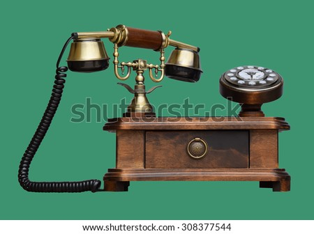 an old telephon with rotary dial on green background - stock photo