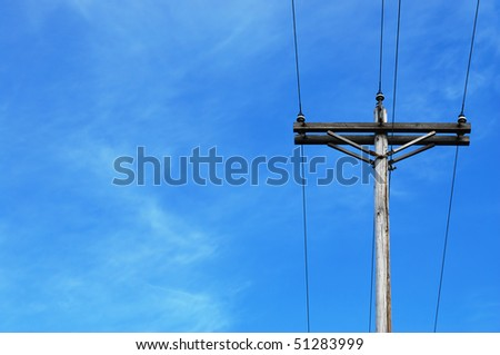 an old telephone pole with wires against blue sky, lots of copy space at left