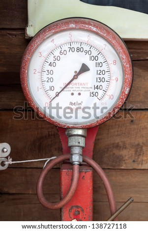 An old tire-pressure measuring gauge - stock photo